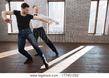 Mastering right dance position of legs. Positive gifted professional dance instructor teaching senior man while having training session and demonstrating new dance step