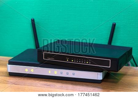 network switch stacking on wireless router. textured green background