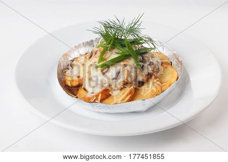 Potato with mushrooms baked in foil on a white background isolated