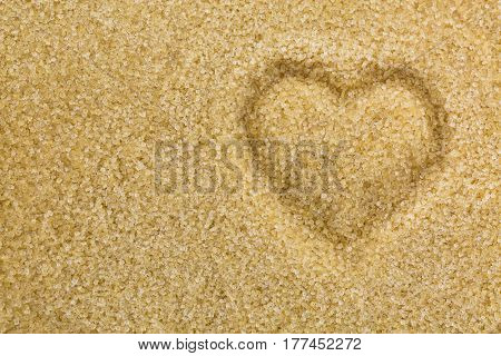 Top view of heart shaped on unrefined unbleached Crystalline sugar in crystal brown color. Conceptual photo for sweet love