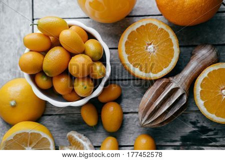 Top View Of Kumquat In A White Bowl, Oranges, Lemons And Fresh Juice Squeezer On Wooden Board.