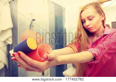 Happy Woman Holding Hair Rollers In Bathroom