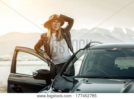 Woman at spreeng time. Young happines female in hat and sunglasses stay near her black car at sunny day.