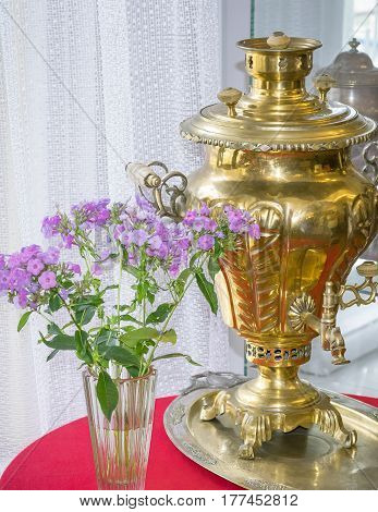 Ancient device for making tea and vase of flowers by the window. The concept of home tea in the family circle.