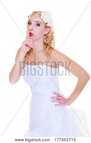 Wedding celebration concept. Bride in white wedding dress showing silence sign having some secret