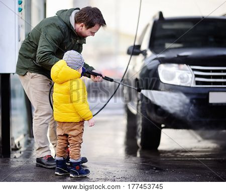 Middle Age Man And His Little Son Washing A Car On A Carwash