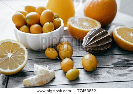 Kumquat In A White Bowl, Oranges, Lemons And Fresh Juice Squeezer On Wooden Board.
