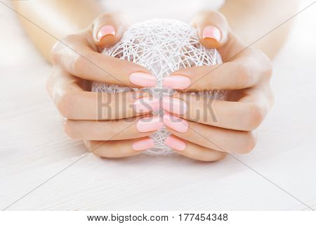 pink manicure with a white ball of yarn on the white wooden table.