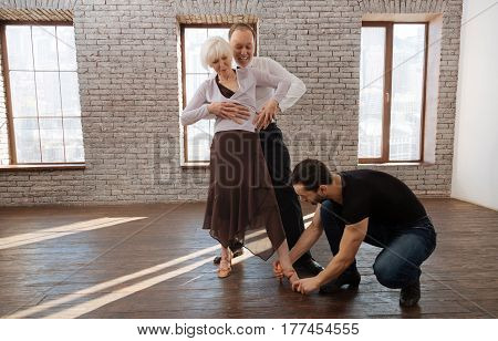 Learning new dance step. Careful mature professional dance instructor teaching elderly couple while having training session and demonstrating dance step