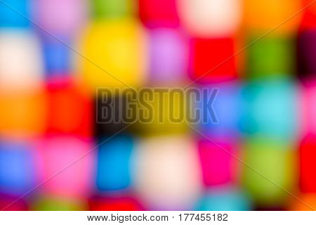 Abstract blurred color wool background - balls of synthetic wool yarn - geometric rainbow pattern - natural defocused lens bokeh