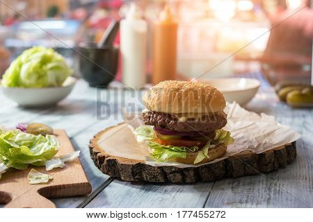 Burger on wooden board. Hamburger on gray table. Eat daily norm of calories.