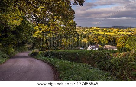 Scenic landscape of the eastern part of Devonshire. The road two white houses and hills in the distance. England