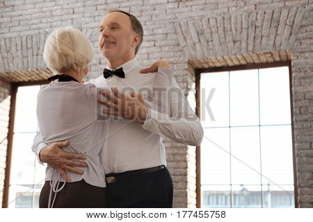 Enjoying new hobby together. Talented smiling positive aging dance couple waltzing in the dance studio while showing dance skills and expressing happiness