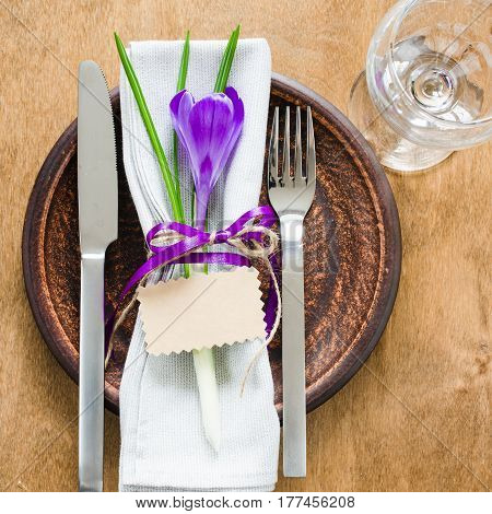 Spring Festive Table Setting With Fresh Flower and Empty Card. Napkin plate and cutlery on wooden table. Holidays background. Selective Focus.