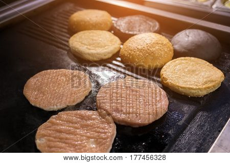 Pan with raw burger meat. Sliced sesame buns. Fry to the crisp.