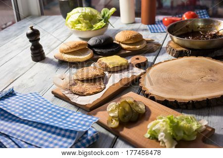 Table with burger ingredients. Buns, lettuce and meat. How to make a cheeseburger.