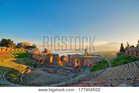 Ancient Theatre Of Taormina With Etna Erupting Volcano At Sunset