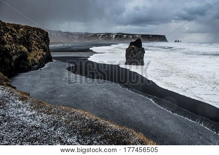 Ice rain in hail in Kirkjufjara black beach Iceland makes natural layers. In Iceland you can have 3 climates in just 10 minutes.