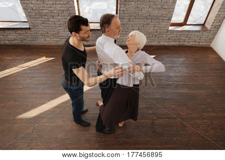 Practicing tango together . Careful athletic capable dance couch teaching aged pensioners tango while having training session and expressing care