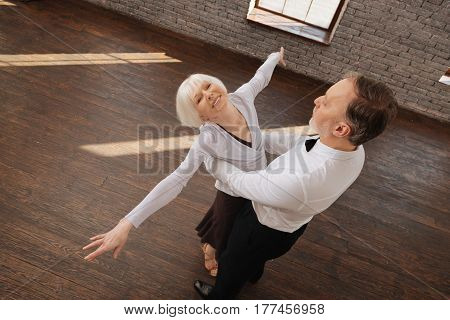 Flying like a bird. Talented optimistic happy senior dance couple waltzing in the dance studio while showing dance skills and expressing joy