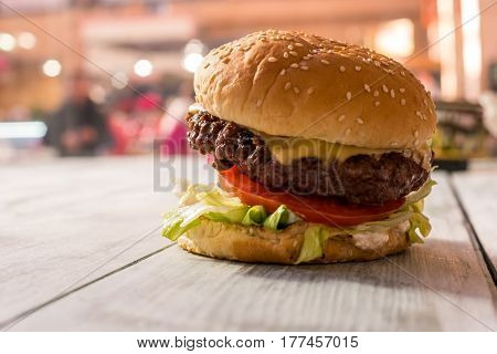Burger on gray wooden surface. Side view of a hamburger. Feast for stomach.