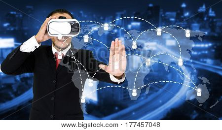 Young asian businessman wearing VR virtual reality headset, business and technology concept for future with world map social media connection on blurred night city background, color tone effect.