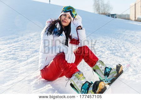 Athlete in sportswear sits on ski slope with snowboard