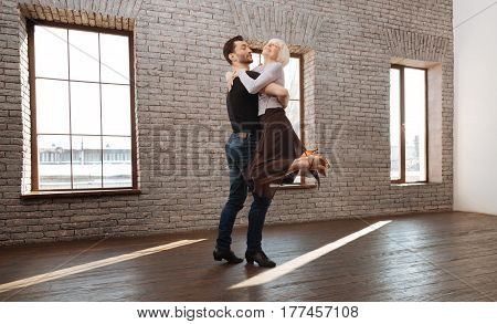 Full of delightful emotions. Professional athletic strong dance instructor teaching elderly woman salsa while dancing and demonstrating new step