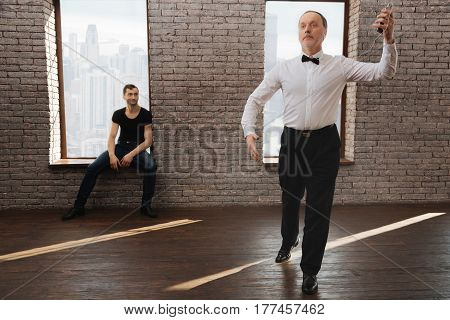 Watching and analyzing students successes . Professional attentive observant dance instructor teaching elderly man waltz while sitting and looking at his performance