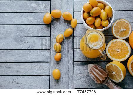 Question Mark Of Kumquat, Oranges, Lemons And Fresh Juice Squeezer On Wooden Board.