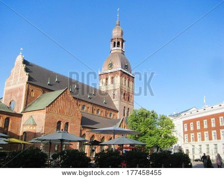 View of Riga Cathedral from local old town square in the morning sun light. Evangelical Lutheran ancient church in Riga, capital of Latvia, popular touristic place.