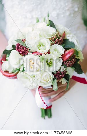 Bride in a white wedding dress holding a flowers bouquet from white rose and red fresh peppers in hands. Wedding bridal bouquet on a white background close up.