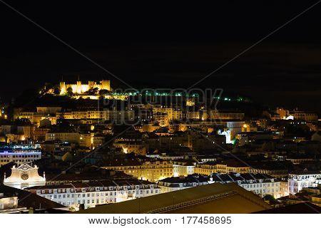 Cityscape of Lisbon, Portugal, with the Sao Jorge Castle seen from Miradouro Sao Pedro de Alcantara at night.