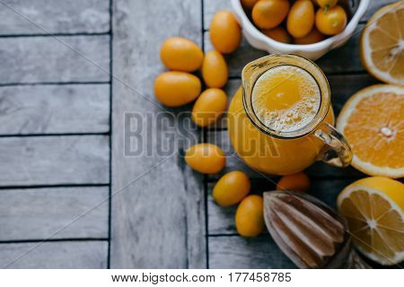 Space For Text: Kumquat In A White Bowl, Oranges, Lemons And Fresh Juice Squeezer On Wooden Board.