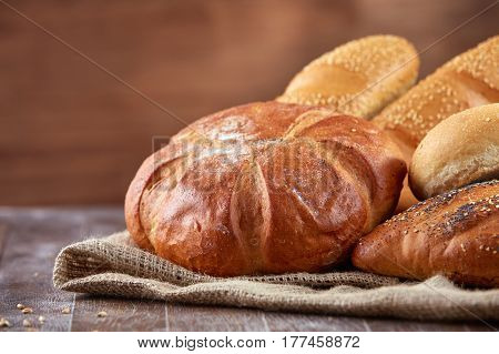 Assortment of baked bread on wooden table background. Natural products. Delicious food. Bread and baked goods on the brown background. Bakery and pastry.