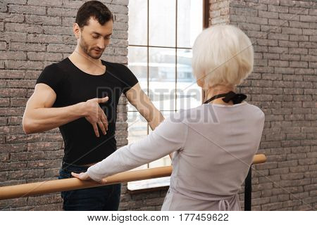 Warming up before dancing together. Athletic artistic involved dance couch teaching aged woman while standing next to the barre and demonstrating right posture