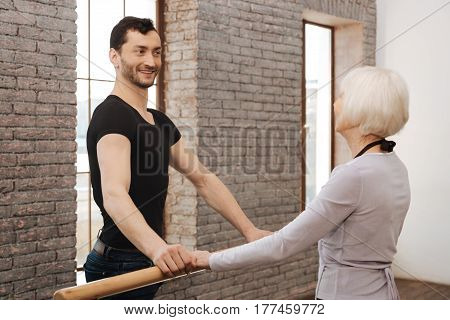 With positive attitude to everything. Athletic happy cheerful dancer teaching aged woman while standing next to the barre and demonstrating right posture