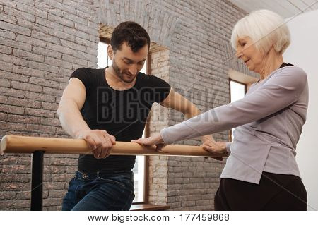 Enjoying first ballet class. Positive helpful skillful dancer teaching aging woman while standing next to the barre and demonstrating right posture