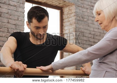 Working hard for success. Serious thoughtful concentrated dancer teaching elderly woman while standing next to the barre and demonstrating right posture