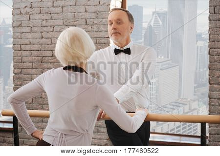 With all my enthusiasm . Optimistic charming happy aging man tangoing with age woman in the dance studio while expressing feelings
