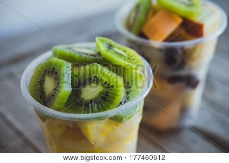Closeup Cut Fruits:kiwi, Pineapple, Tangerines, Apples, Melon In Plastic Cups On The Wooden Table