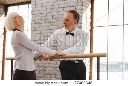 Full of joyfulness. Creative inspired retired couple dancing in the dance studio while expressing joy and standing next to the barre