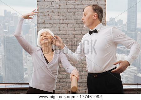 Pleasure to be next to you. Romantic joyful old couple performing in the art studio while having fun and standing next to the barre