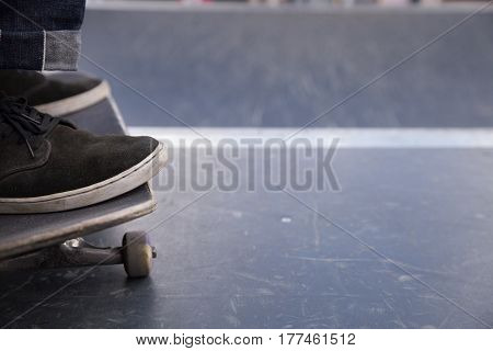 Closeup of man's foot on skateboard. skater riding a skateboard. view of a person riding on his skate.