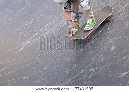 Closeup of kid boy's foot on skateboard. skater riding a skateboard. view of a person riding on his skate. Sport and active life concept