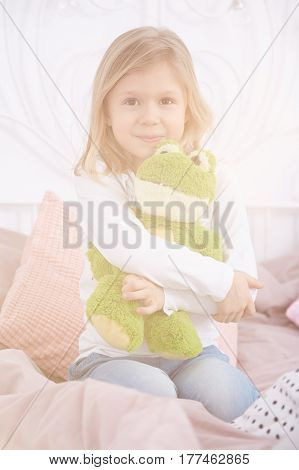 Little girl sitting on a bed and hugging her frog mascot