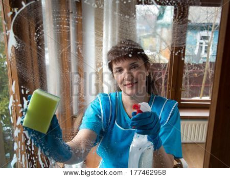 woman with gloves washes a window pane