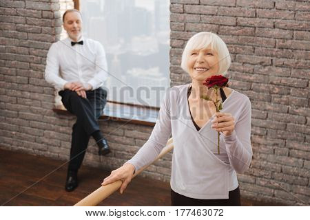 With love in every step. Delighted upbeat retired woman performing in the dance studio next to barre and mastering dance skills while her aged dance partner sitting in the background