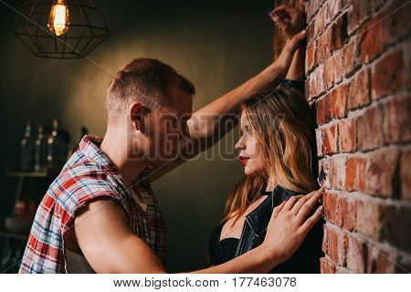 Handsome man and sexy woman standing beside wall