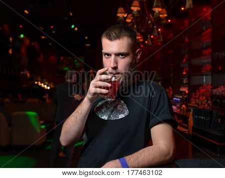 White young handsome bearded man with cocktail in the nigth club
